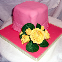 Borders Rose Cake This pink fondant covered cake has fondant garrett-frilled skirting at the bottom of the cake. Yellow roses of various sizes are front and...