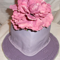 Tera Peony Cake This large fuschia-colored peony sits atop a violet fondant covered cake. Crimpers were used to decorate the cakeboard.