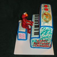 Elmo's World Piano Piano and stool are cake covered in fondant. Elmo is candy clay and fondant. Fish bowl is first attempt at poured sugar.