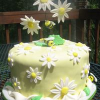 Daisies And Bees Cake covered in fondant. Flowers and bees made with gumpaste.