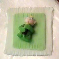 Baby   3-D out of fondant, of a baby clasping a bottle on his blankie. I made this for a baby shower cake. Baby is handmade, without a mold.