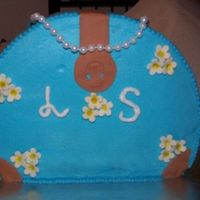 My First Purse Cake This cake is decorated with butter cream frosting and gumpaste flowers. I used fondant to make the strap and buckle on the purse. The...