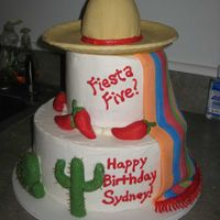 "Fiesta Five Birthday Cake 10"" and 6"" rounds with mini wonder mold cake in sombrero, covered in BC. Fondant blanket, sombrero, peppers, cacti."