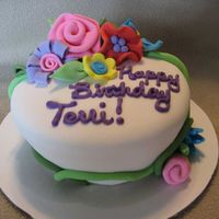 "Whimsical Flower Cake 6"" carved cake covered in fondant with whimsical fondant flowers"