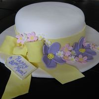 "Floral Hat 8"" round WASC with lemon curd filling covered in fondant with fondant flowers and sugarpaste bow."