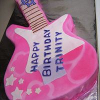 Pink Guitar Cake Hannah Montana inspired guitar cake. Cake is hand carved and covered in fondant.