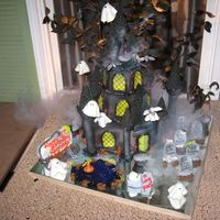 Haunted Castle I made this for my neice's birthday. I used wiltons castle kit and my imagination. Hanging ghost and bats from the top, graveyard...