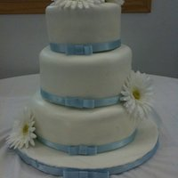 Blue Ribbon And Daisies basic cake 10,8 and 6 inches with fondant and ribbon. Silk flowers.