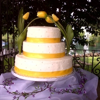 Tulip Wedding Cake Piña colada flavor, cream cheese icing, satin ribbon, comestible pearls, and yellow tulips. Match with the decoration.