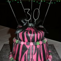 Pink Zebra Stripes With Black Metallic Bow. semi topsy turvy cake. pink with zebra stripes and black metallic bow.