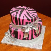Pink Zebra Print semi topsy turvy cake - pink with zebra print and silver fondant ribbon and bows.