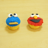 Elmo And Cookie Monster Cupcakes  fondant covered cupcakes. The Fur on cookis monster was done pulling up and out on the fondant such that the fondant would stand out like...