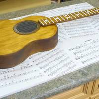 Guitar Cake  Sheet cake carved by hand with a handrawn template. Painted with food coloring. The cake board is foam core covered in printed guitar sheet...