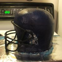 Football Helmet Cake  A disaster from the start! The gumpaste face mask broke and I had to use a real one, but the biggest problem I had was with the frosting....