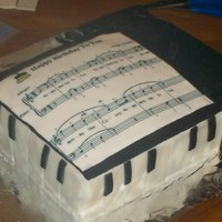 Piano And Sheet Music Cake 8X8 square cake with buttercream icing.Edible image of happy birthday sheet music on top(with birthday boys name inserted). Fondant piano...