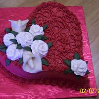 Kelli_Bd_Cake_2~0.jpg I Used a Wilton Heart Shapd pan. Decorated with wilton red red color.Buttercream icing with fresh strawberry/cream cheese filling. Roses...
