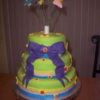 Butterflies And Daisies Fondant covered cake with daisies and butterflies.