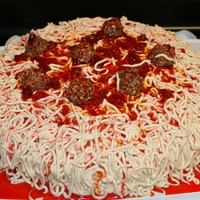 "Spaghetti And Meatballs   12"" round single layer cake. Buttercream piped for noodles, strawberry topping for sauce, and chocolate truffles for the meatballs"