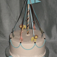 Circus Carousel buttercream cake with fondant accents. The animals are paper (from a kit the client bought).