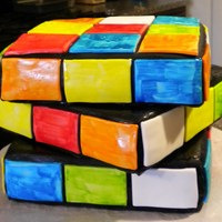 Rubik's Cube Cake: 3 - 8 inch squares covered in black fondant. Square tiles made from fondant, and hand-painted w/ food coloring. This was fun to make...