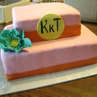 Colorful Monogram Cake Two tier cake covered in pink vanilla fondant. Orange fondant borders. Teal tinted gumpaste flower. Yellow gumpaste plaque with monogram...
