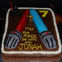 Dueling Light Saber Cake  My 7 year old wanted two light sabers fighting. 11x15 cake (1/2 choc/1/2 yellow), chocolate buttercream, lightsabers formed with brownie...