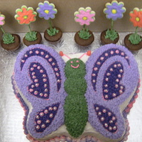 Butterfly With Flowers buterfly cake made with wilton cake pan decorated with buttercream and the flowers are mini cupcakes with flower cookies!
