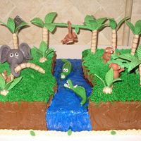 Fun In The Jungle This cake has a hand carved river with fondant aligators. The gumpaste monkeys are trying to cross the river and they have enlisted the...