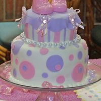 Polka Dots And Stripes Baby Girl Shower Cake  Cake is vanilla with fondant covering and fondant dots and stripes! The booties are just cute little ceramic booties I found at Hobby Lobby...