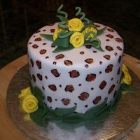 Leopard And Yellow Roses Leopard print painted fondant with yellow ribbon roses.
