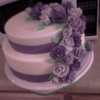 Wedding Bliss Wilton course 3 finale cake...2 tiers covered with fondant and border done with colored fondant strips...2 hues of purple roses done with a...
