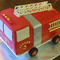 Firetruck Cake  Marble scratch cake w/cookies & cream filling, vanilla bc, and white chocolate fondant. Oreo wheels & white chocolate ladders. TFL...