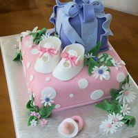 Booties For Baby This in baby shower cake, tiers made to look like gifts boxes with baby Booties, daisies and a pacifier made out of fondant.