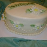 Daisy Birthday Cake Lemon cake with filling of thick lemon pudding mixed with whipped topping, buttercream frosting, flowers, leaves, and banner of fondant.