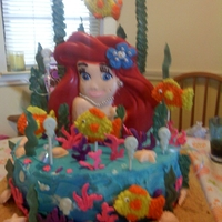 Ariel the ariel standing up on the cake is a candy plaque. the cake was 3 layers - caramel, white and chocolate. the sand is graham crackers, the...
