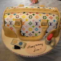 Louis Vuitton Purse Cake  This is my first attempt purse cake. Cake carved and covered with fondant. Louis Vuittondesigns is hand painted with food coloring markers...