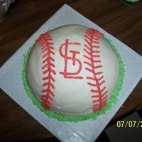 Grooms Cake For Fan Of St. Louis Cardinals  cake is white, made from the Wilton sports ball pan, into a baseball, with the STL Cardinals logo piped on, and grass around the border of...