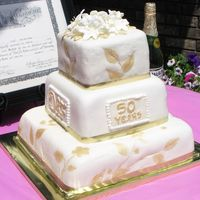 50Th Wedding Anniversary First cake for an event. I gave it to them as a gift to practice. White fondant with gold accents. Any suggestions on how to improve are...