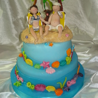 Funny Wedding Cake! This cake was made with the couple on the beach, your pet and chairs that they use when traveling. It was fun the marine theme. The shells...