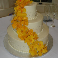 Yellow Orchid Wedding Cake  Not my design at all. The bride gave me a picture and I did the best I could. 6, 10, and 14 inch cakes iced with cream cheese icing and...
