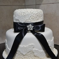 White Lace White lace cake with black bow.Lemon poppy seed with white chocolate chunk filling.
