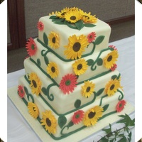 Sunflower And Gerber Daisy Wedding Cake  My husband and I made this wedding cake for a bride who loved sunflowers. The cake is two flavors. It has alternating layers of WASC with...