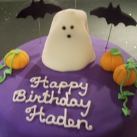 Halloween Birthday Cake for a boy celebrating his birthday on Halloween. Ghost is fondant with a Gum Sucker underneath. Pumpkins and bats are fondant. Border...