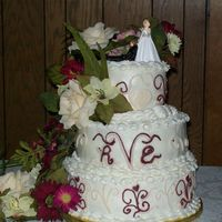 Vincent Wedding 3 tier yellow and chocolate cake with buttercream icicng and freehanded scroll work.Flowers are silk.