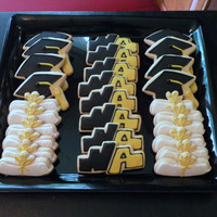 Graduation Cookies! Sugar cookies with glaze icing. NA cookies are handcut from school logo. Circle cookies with grad cap- cap is cut from Duff's fondant...