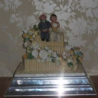 White Chocolate Cigarillo Cake With Models 3 tier square sponge cake with qhie chocolate cigarillos, sugar flower spray and modelled married couple
