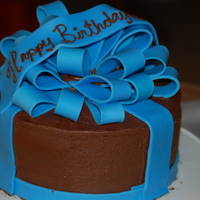 Blue And Brown Gift   Chocolate icing with blue fondant bow. First attempt to make a bow like this. My mother loved it.