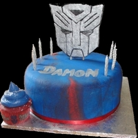 Autobot Birthday This was for my stepson's 8th birthday. The mask is a fondant plaque with fondant pieces hand cut and placed together on the plaque to...