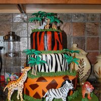 Safari Birthday Three tiered cake with 10, 8, and 6 inch tiers. All three tiers are lemon cake with lemon filling covered in lemon buttercream and MMF.