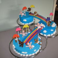 Diaper Downpour The cake is covered in buttercream and the babies / rainbows are made of fondant.